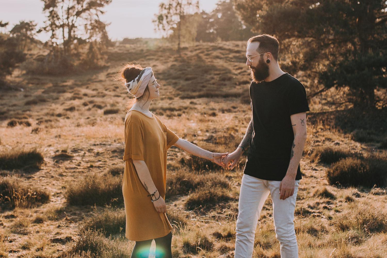 Paar hält sich bei Sonnenuntergang in einer Heidelandschaft an den Händen